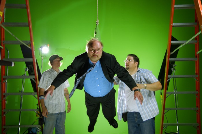man hanging from a rope against a greenscreen in a bts shot of a film shoot