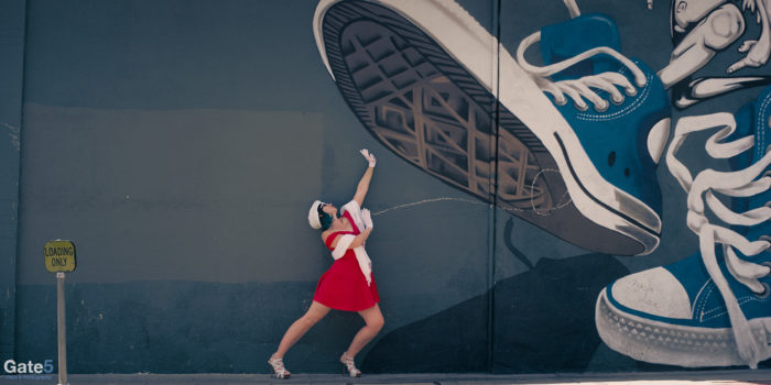 woman in red dress appears to be stepped on by big sneaker