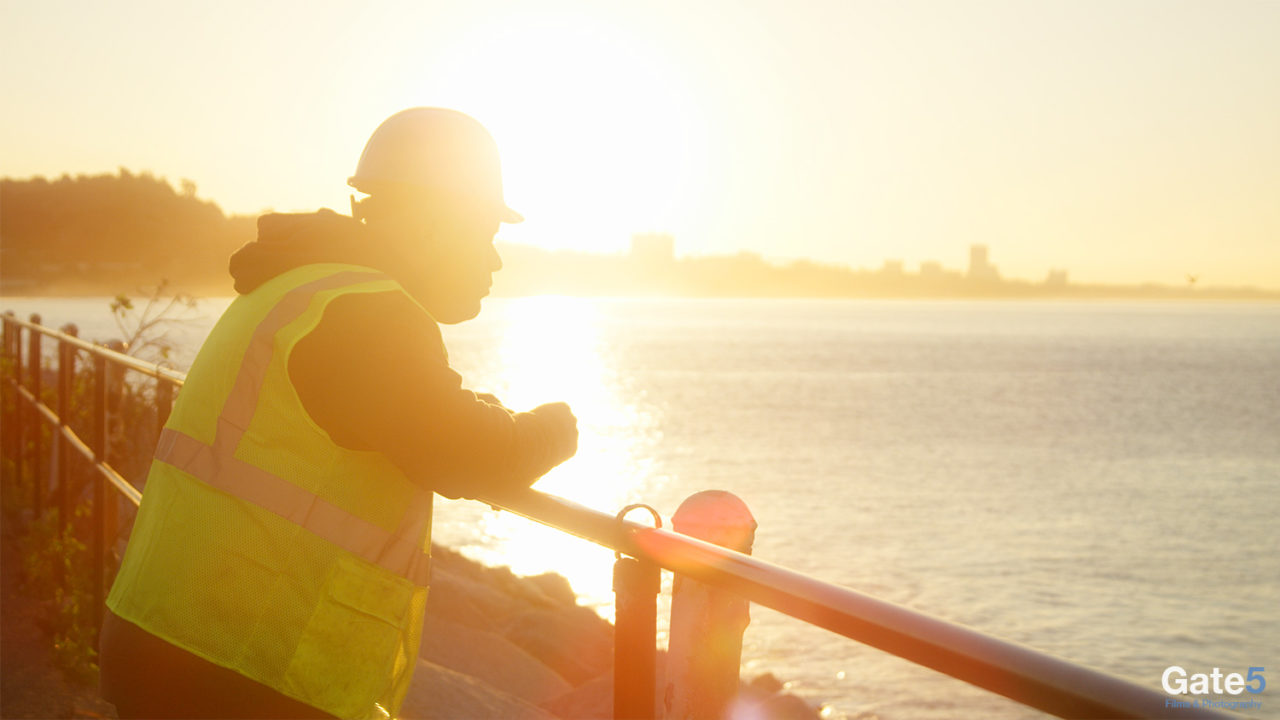 a construction worker looking out at the ocean in the morning sunrise