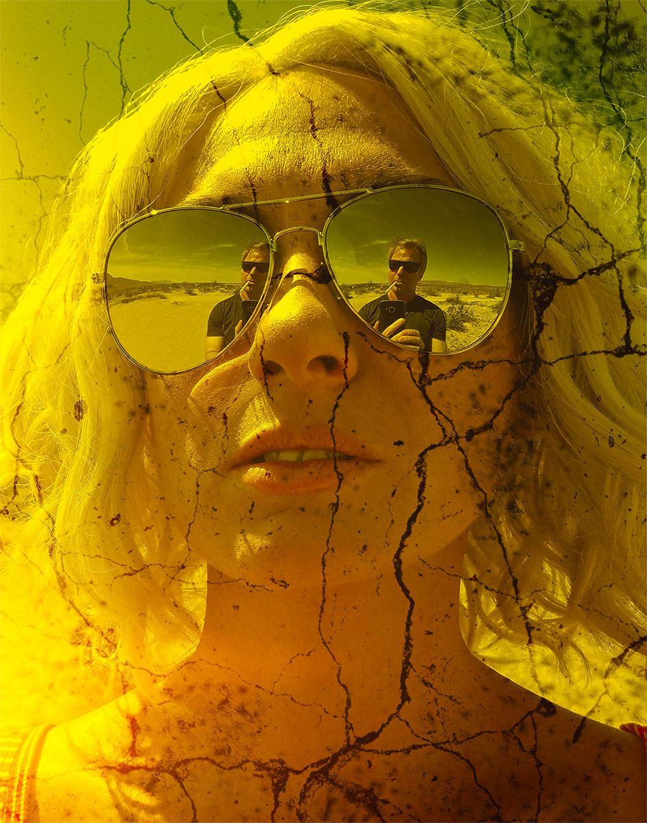 The reflection of a man smoking in a blonde woman's mirrored sunglasses