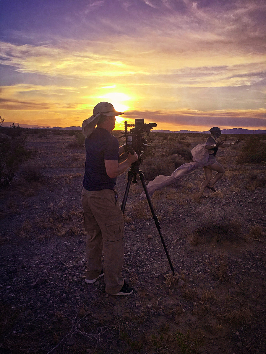 an alien runs past camera at sunset in the desert in BTS shot