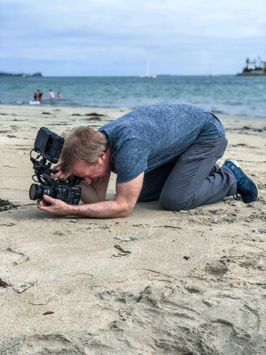 film director shoots model on the beach on the sand