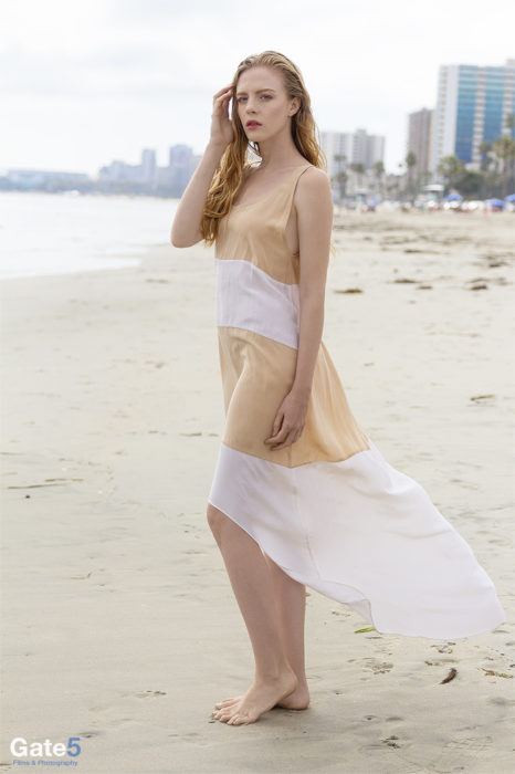 fashion photography of model wearing pretty dress on the beach
