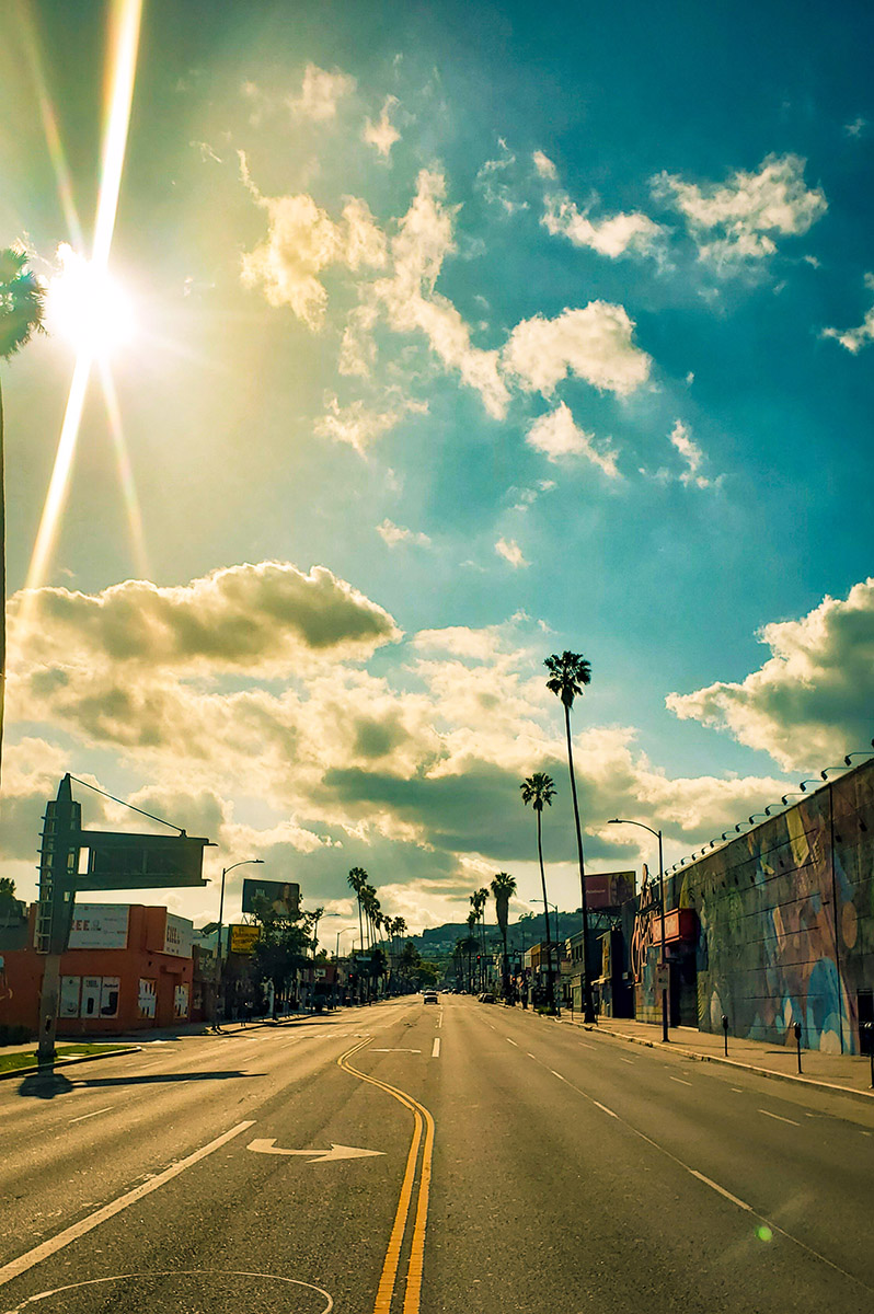 An empty Sunset Blvd in Hollywood during Coronavirus stay at home order on a sunny day with puffy clouds