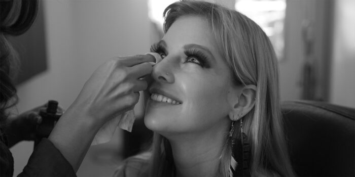 black and white behind the scenes shot of a model getting eyelashes