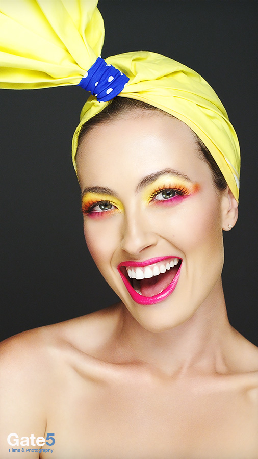 model in beauty video smiling with red lips and color makeup