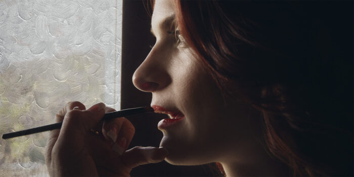 a female readhead actor gets her makeup done by window light