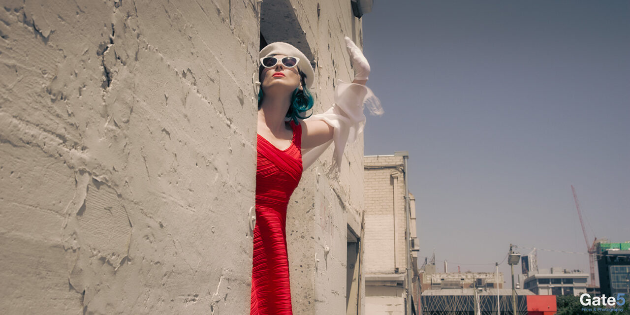 a woman in a red dress waves from a door in a building