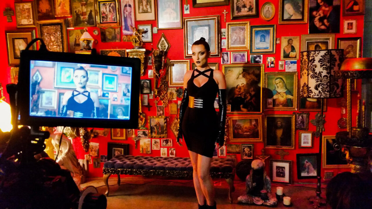 a woman stands in front of a red wall in a fashion film directed by Greg McDonald